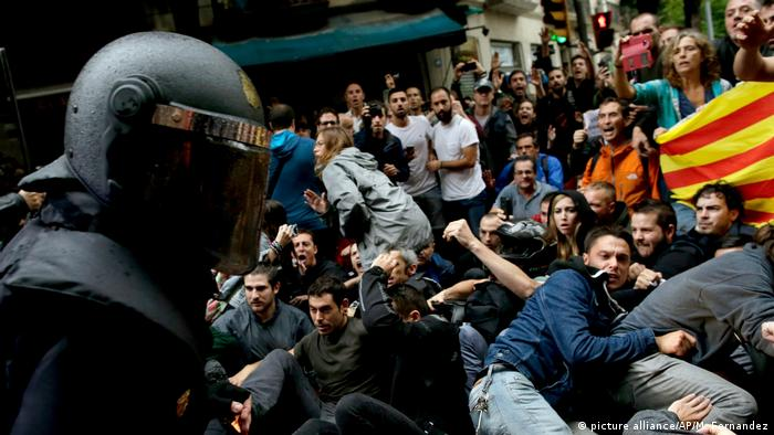 A crowd of people keeps a distance from a member of the Guardia Civil in Barcelona on October 1