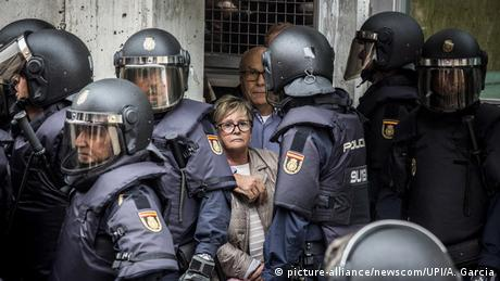 A woman is surrounded by Spanish police on October 1 during the Catalan independence referendum.