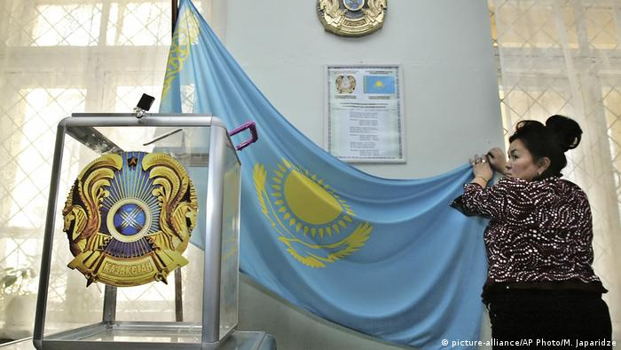 An election commission official adjusts a national flag at a polling station (picture-alliance/AP Photo/M. Japaridze)