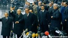 Presidential adviser Dr. Henry Kissinger, third from left, and Hanoi's Le Duc Tho, waving, are seen after their last meeting at the International Conference Center in Paris, Jan. 23, 1973. (AP Photo)  
