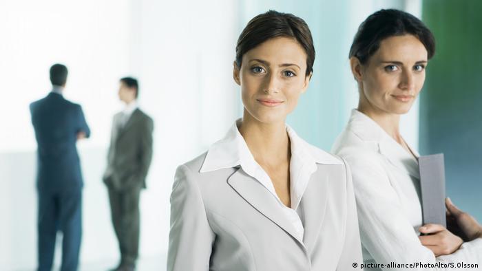 Geschäftsfrauen mit Männern im Hintergrund (picture-alliance/PhotoAlto/S.Olsson)