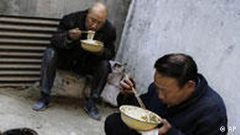 **FILE** In this March 13, 2008 file photo, workers eat lunch near a construction site in Beijing. An estimated 20 million migrant workers have lost jobs because of the global economic crisis, a government official said Monday, Feb. 2, 2009, giving the government a huge worry as it tries to maintain social stability. (AP Photo/Oded Balilty, File)