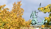 Die Quadriga mit der Siegesgöttin Viktoria auf dem Brandenburger Tor ist am 22.09.2017 hinter dem herbstlich gefärbten Laub einiger Bäume zu sehen. Foto: Ralf Hirschberger/dpa-Zentralbild/ZB | Verwendung weltweit