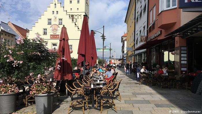 People sit outside in cafes in the Bavarian town of Deggendorf