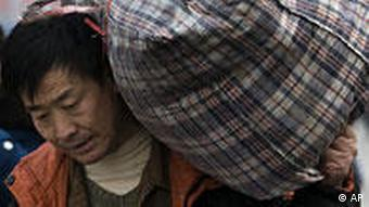 A migrant worker carries his bags as he leave the Beijing Railway Station, China, Tuesday, Dec. 16, 2008. World Bank President Robert Zoellick warned Monday that 2009 will prove to be a very difficult year for China and the world amid the financial downturn, but said the Chinese government's efforts to shore up the country's own economy will help aid global stability. (AP Photo/Andy Wong)