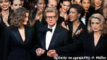 (FILES) French designer Yves Saint-Laurent (C) salutes the crowd with French model Laetitia Casta (L) and French actress Catherine Deneuve (R) at the Centre Georges Pompidou art gallery in Paris, where the last Haute-Couture show ever of the designer took place. Yves Saint Laurent, one the top French designers of the 20th century, died in the evening on June 01, 2008 in Paris, the Pierre-Berge-Saint Laurent Foundation said. The reclusive French maestro, who had retired from haute couture in 2002 after four decades at the top of his trade, had been ill for some time. AFP PHOTO JEAN-PIERRE MULLER (Photo credit should read JEAN-PIERRE MULLER/AFP/Getty Images)