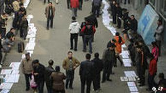 Migrant workers place their job applications on the ground to attract employers outside a labour market in Chengdu, China, Monday, Feb. 2, 2009. The global economic crisis has taken hold deep in China's impoverished countryside, as millions of rural migrants are laid off from factory jobs and left to scratch a living from tiny landholdings _ creating unsettling prospects for a government anxious to avoid social unrest. (AP Photo/Color China Photo) ** CHINA OUT **