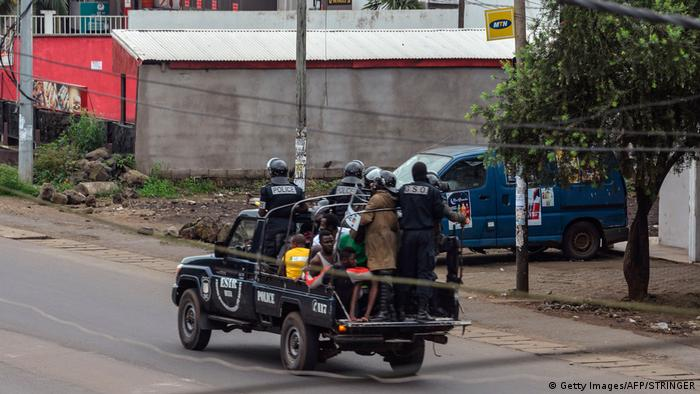 Cameroon police drive in van with arrested protesters