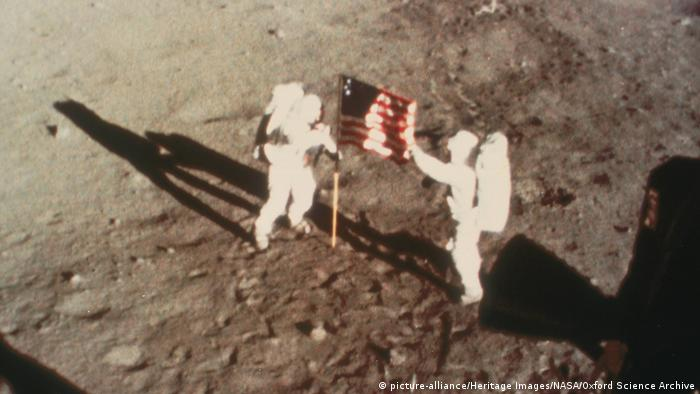 Armstrong and Aldrin unfurl the US flag on the moon.