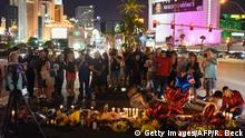 03.10.2017 People gather and light candles at a makeshift memorial near the Mandalay Hotel on the Las Vegas Strip, in Las Vegas, Nevada on October 3, 2017, after a gunman killed 58 people and wounded more than 500 others, before taking his own life, when he opened fire from a hotel on a country music festival. Police said the gunman, a 64-year-old local resident named as Stephen Paddock, had been killed after a SWAT team responded to reports of multiple gunfire from the 32nd floor of the Mandalay Bay, a hotel-casino next to the concert venue. / AFP PHOTO / Robyn Beck (Photo credit should read ROBYN BECK/AFP/Getty Images)