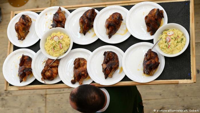 Konobar s pladnjem na kojem je deset tanjura i dvije zdjele