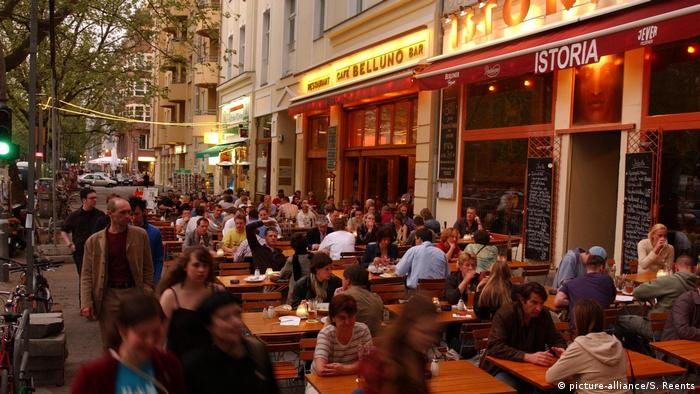 People sit at a street cafe in Berlin (picture-alliance/S. Reents)