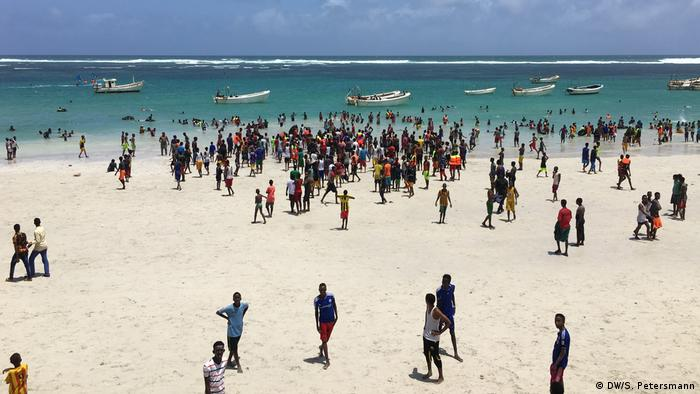Crowds in the foreground and boats in the water at Liido beach (DW/S. Petersmann)