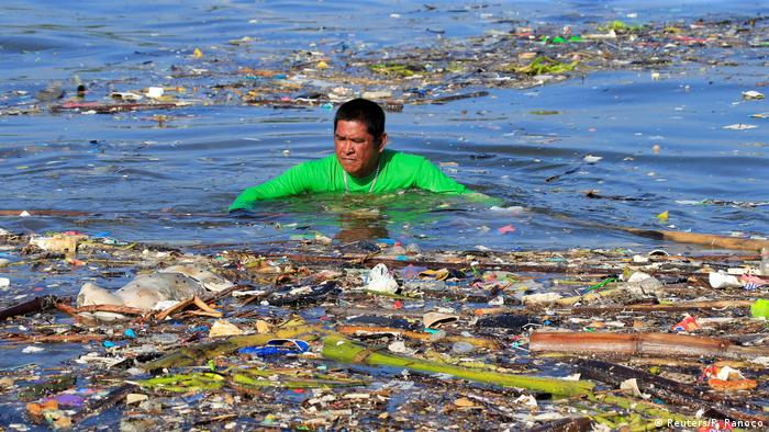 A man collects garbage along the coast of Manila bay by swimming through garbage