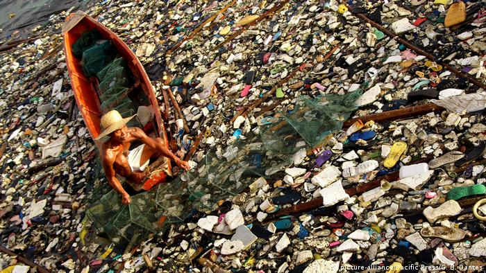 A fisherman in the Philippines removes a fish and crab trap from plastic-filled waters.
