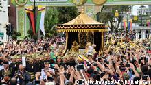 05.10.2017 +++ Brunei's Sultan Hassanal Bolkiah (center-L) and Queen Saleha (centre-R not visible) wave from the royal chariot during a procession to mark his golden jubilee of accession to the throne in Bandar Seri Begawan on October 5, 2017. Brunei's all-powerful sultan will mark 50 years on the throne Oct 5 with lavish celebrations including a glittering procession, a 21-gun salute and a ceremony at his vast, golden-domed palace. / AFP PHOTO / ROSLAN RAHMAN (Photo credit should read ROSLAN RAHMAN/AFP/Getty Images)