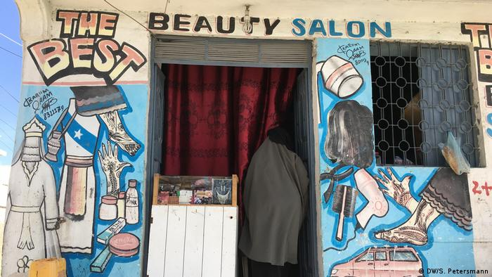 The painted front of a beauty salon shows pictures of beauty products, dresses, henna adorned hands and feet (DW/S. Petersmann)
