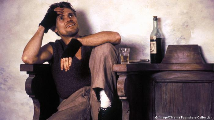 Film still 'The English Patient'': Willem Dafoe sitting on a massive wooden chair with a glass and bottle of alcohol next to him. (Imago/Cinema Publishers Collection)