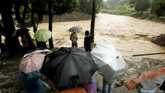 People look at the Tiribi river flooded after heavy rains by Tropical Storm Nate in San Jose, Costa Rica