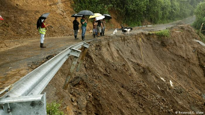Residents look ta road partially collapsed by heavy rains of Tropical Storm Nate that affects the country in El Llano de Alajuelita, Costa Rica
