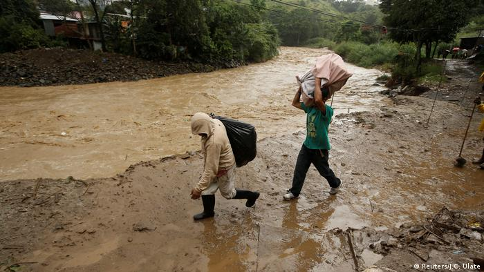 People recover their belongings after flooding caused by heavy rains of Tropical Storm Nate that affects the country in San Jose, Costa Rica