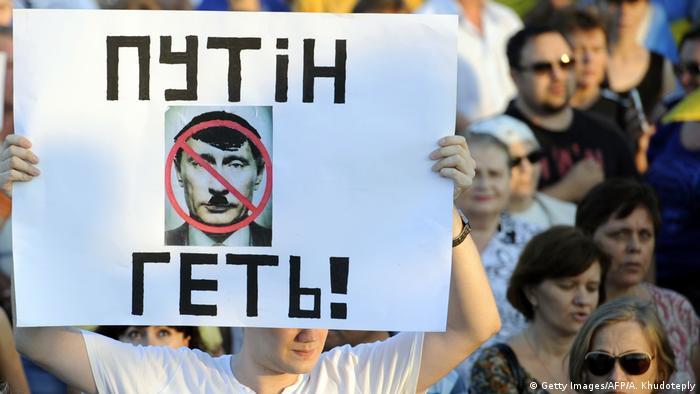 Мужчина держит плакат с надписью Путiн геть!, 28 августа 2014 года