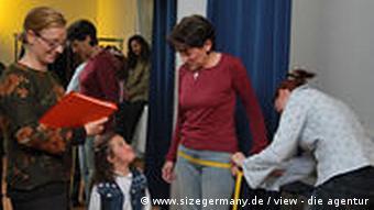 Frau wird vor einem Spiegel an der Hüfte mit einem Maßband vermessen, Quelle: www.sizegermany.de