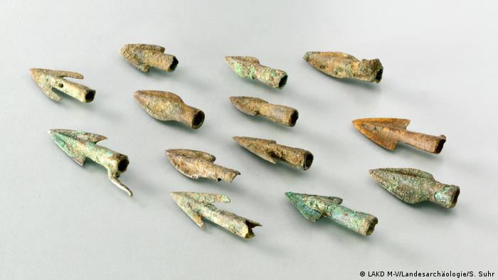 Several arrow tips lined up on a white board (Foto: LAKD M-V/Landesarchäologie/S. Suhr)