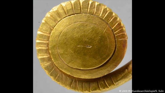 Gold brooch in front of a gray background (Photo: LAKD M-V/Landesarchäologie/S. Suhr)