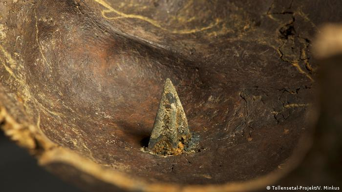 An arrow tip stuck in a dark-colored skull (Photo: Tollensetal-Projekt/V. Minkus)