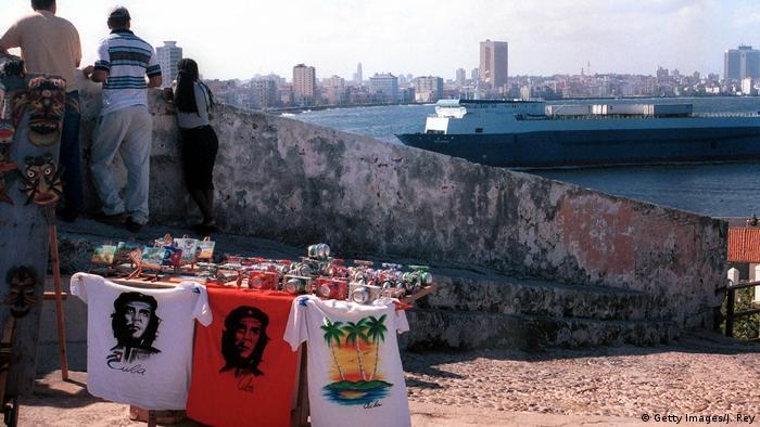 T-Shirts mit dem Gesicht Che Guevaras an einem Verkaufsstand, im Hintergrund eine Mauer und ein einfahrendes Schiff, dass in im Hafen von Havanna ankommt (Foto: Getty Images)