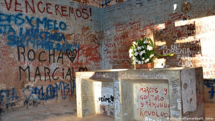 Ein Steinblock, darauf weiße Blumen. Die Wände sind vollgeschrieben mit Losungen, Namen und Daten (Foto: Picture Alliance)
