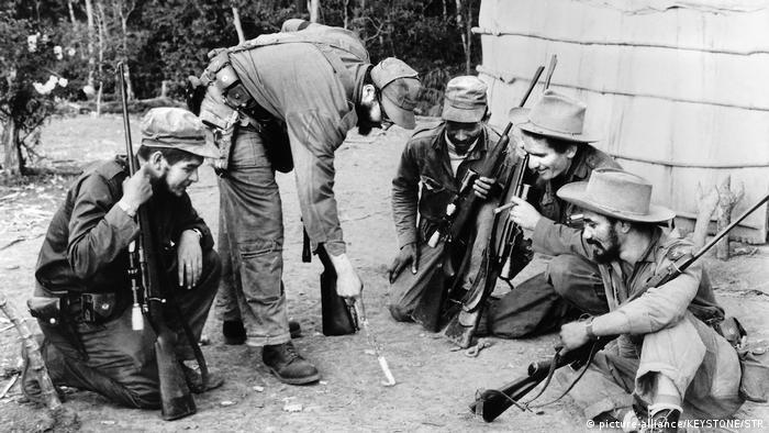 Fidel Castro zeichnet gebückt etwas mit einem Stock in den San, um ihn herum Knien und sitzen vier Männer mit Gewehren (Foto: Picture Alliance)