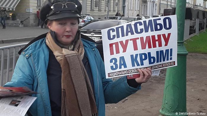 Активистка Национально-освободительного движения раздает листовки в поддержку президента Путина рядом с Марсовым полем