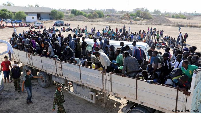 Migrantes em camiões antes de serem transportados para um centro de detenção na Líbia
