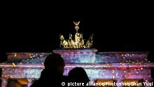 (171006) -- BERLIN, Oct. 6, 2017 () -- Visitors look at the illuminated Brandenburg Gate during the Festival of Lights in Berlin, capital of Germany, on Oct. 6, 2017. Berlin turned into a city of light art with the opening of its Festival of Lights on Friday which will last from Oct. 6 to 15. (/Shan Yuqi)  