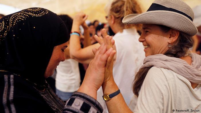 Arab and Israeli women touch hands near the Jordan river