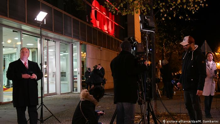 Media teams wait outside the CDU center