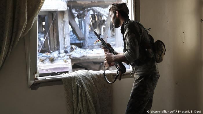 A SDF fighter peers through a window on the front line in Raqqa