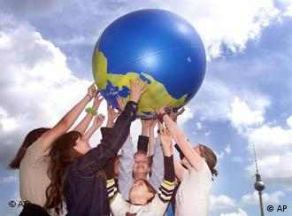 Молодые люди держат в руках модель Земли