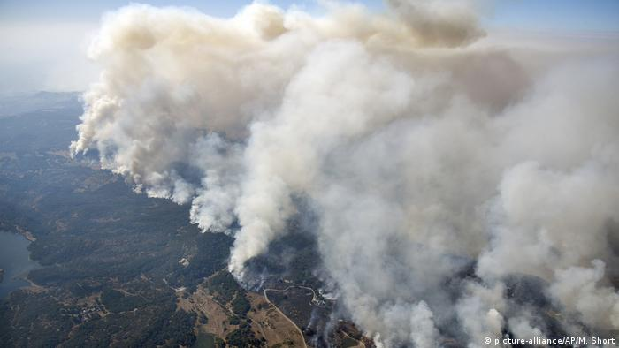 An aerial view shows wildfires spewing smoke northeast of Napa in California's wine district