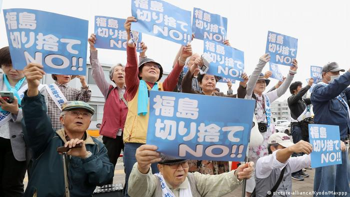Plaintiffs suing the state and TEPCO over the 2011 nuclear crisis, hold up signs in front of the Fukushima District Court (picture-alliance/Kyodo/Maxppp)