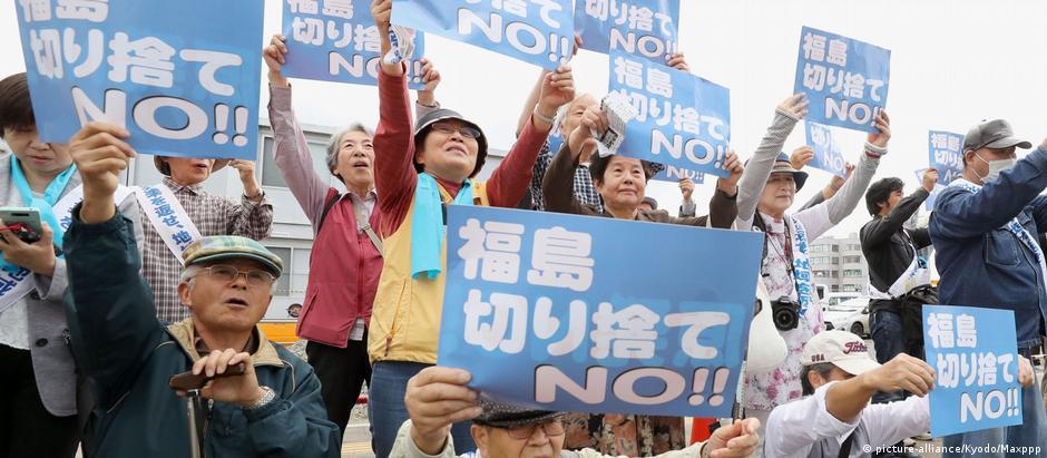Alguns dos 3.800 requerentes da ação coletiva seguram cartazes do lado de fora do tribunal distrital de Fukushima