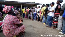 People waiting in line at a polling place in Liberia's first round of voting (Reuters/T. Gouegnon)