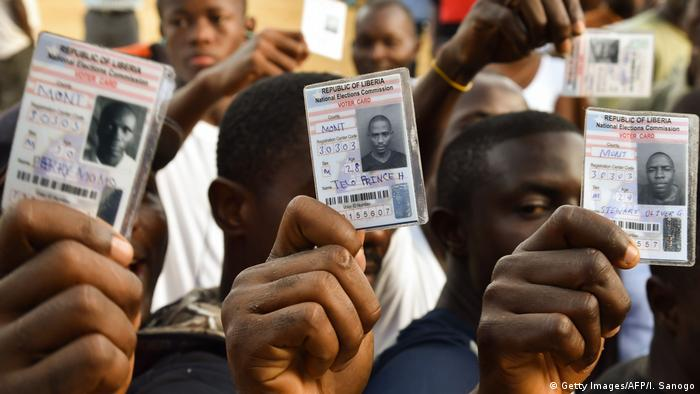 People holding their ID cards (Getty Images/AFP/I. Sanogo)