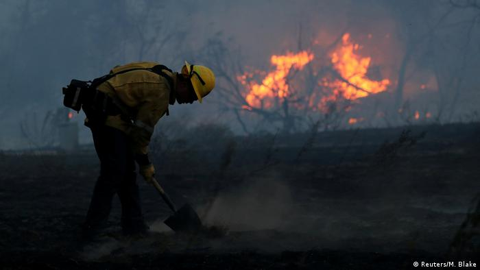 A firefighter works to put out hot spots