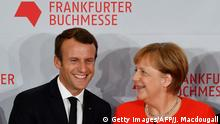 French President Emmanuel Macron and German Chancellor Angela Merkel pose for photogaphers as they arrive to open the Frankfurt Book Fair on October 10, 2017 in Frankfurt am Main, western Germany. France is this year's guest of honour at the world's largest book fair, where more than 7,000 exhibitors from more than 100 countries are expected from October 11 to 15. / AFP PHOTO / John MACDOUGALL (Photo credit should read JOHN MACDOUGALL/AFP/Getty Images)