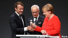 German Chancellor Angela Merkel (R), French President Emmanuel Macron (L) and president of the German Publishers and Booksellers Association Heinrich Riethmueller (C) open the Frankfurt Book Fair on October 10, 2017 in Frankfurt am Main, western Germany. France is this year's guest of honour at the world's largest book fair, where more than 7,000 exhibitors from more than 100 countries are expected from October 11 to 15. / AFP PHOTO / LUDOVIC MARIN (Photo credit should read LUDOVIC MARIN/AFP/Getty Images)