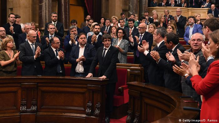 Carles Puigdemont is applauded after his address to the Catalan Parliament