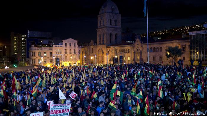 People gather outside the Basilica of San Francisco to mark 35 years of Bolivia's democracy and protest an attempt by President Evo Morales to run for reelection